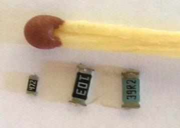 SMD резисторы рядом со спичкой для сравнения масштаба